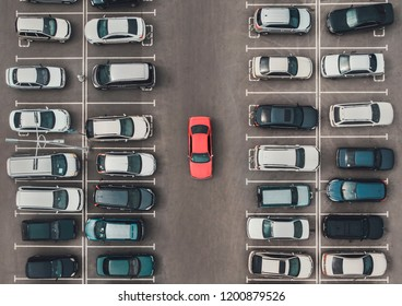 Top view of the crowded Parking lot with quadcopter or drone. Original bright automobile among the grey of mediocre cars. Parking space search, No parking space.