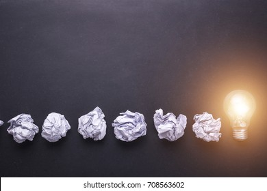 Top view crumpled white paper and light bulbs on black stone board. Create idea concept