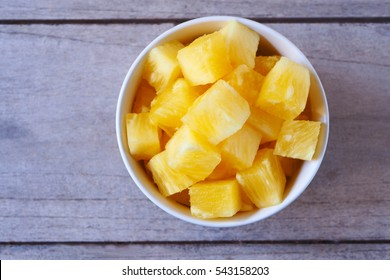 Top view of cube pineapple in a bowl on a wooden table.