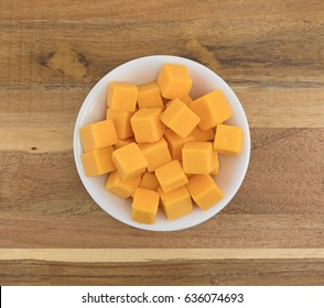 Top view of cubed mild cheddar cheese in a white bowl atop an old wood counter top.