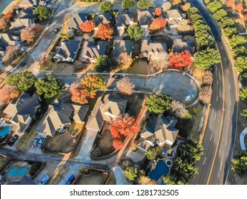 Top view cul-de-sac (dead-end) street at residential neighborhood near Dallas, Texas. Row of single-family houses surrounded with colorful leaves in autumn season
