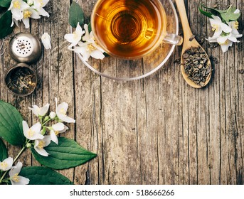 Top view of cup of asian hot green tea and jasmine flower on rustic wooden table with copyspace. Herbal and alternative medicine background.