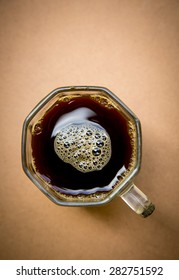 Top view of a cup of black coffee on wooden table