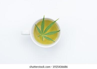 Draufsicht auf Tasse Cannabis-Tee mit grünem Marihuana-Blatt auf weißem Hintergrund, Kopienraum