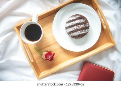 Top view of a cup of coffee with chocolate bread on white background