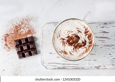 Top view of cup of coffee with cream and cocoa powder and chocolate bar.