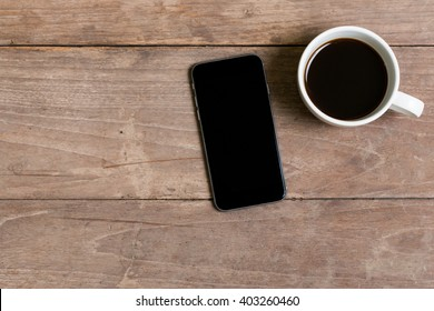 top view cup of coffee and smart phone on old wooden table