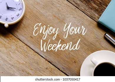 Top view of a cup of coffee,clock,notebook and pen on wooden background written with ENJOY YOUR WEEKEND.