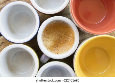 top view of a cup of creamy espresso coffeee next to others empty cups
