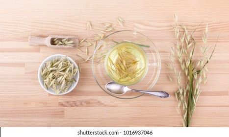 Top view of a cup of fresh oat tea on a wooden background