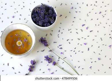 Top view of a cup of herbal tea decorated with fresh and dry lavender herbs on a white background. Porcelain cup of tea drink garnished with lavander and camomile flowers. Photo from above.