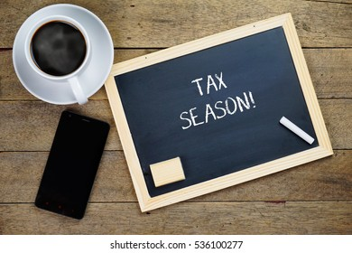 Top view of a cup of hot coffee, smartphone and black chalkboard written with TAX SEASON on old wooden background.