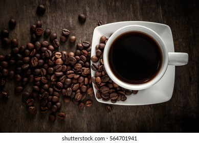 Top view of a cup of hot coffee on wooden rustic table with coffee beans