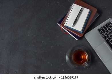 top view of a cup of hot tea on dark table with laptop, and books on the black table. Flat lay of work desk with office accessories. Business or working concept.