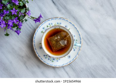 Top view of a cup of  hot tea in a pretty vintage teacup on a marble table