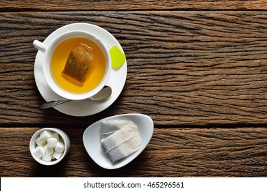 Top view of a cup of tea with tea bag and sugar cube on wooden table