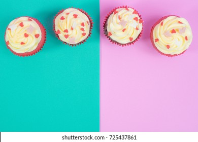Top view of cupcakes in dual colors, green and pink background with empty space for text