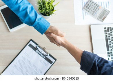 Top view customer and insurance agent shaking hands over investment plan document and calculator as background in the office workplace table.