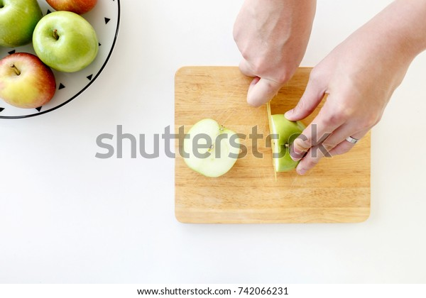 Top view of Cut green apple in half with hands by plastic knife in wooden chopping board with upper left red and green apples in white plate with black triangles pattern on on white background.