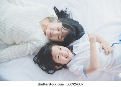 Top view of Cute asian children lying on white bed