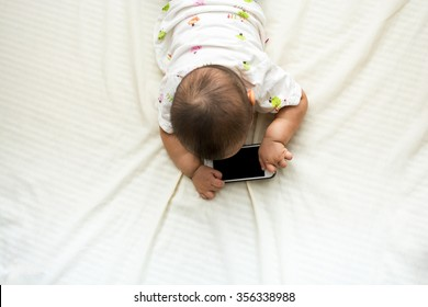 Top view Cute baby playing a smartphone with space