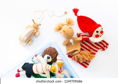 Top view of cute and funny vintage children toys in and besides a blue plastic box on white background. Assortment consists of a clown, a squirrel, a teddy bear, dolls and a wooden snail.