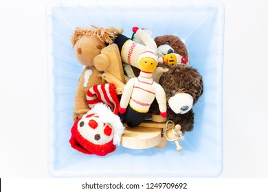 Top view of cute and funny vintage children toys in a blue plastic box on white background. Assortment consists of a clown, a squirrel, a teddy bear, dolls and a wooden snail.
