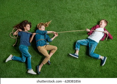 Top view of cute girls and boy lying on grass and playing tug of war