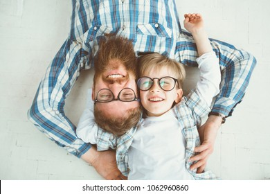 Top view of cute little boy and his handsome young beard dad, both in eyeglasses, smiling while lying with hands behind head on white floor.