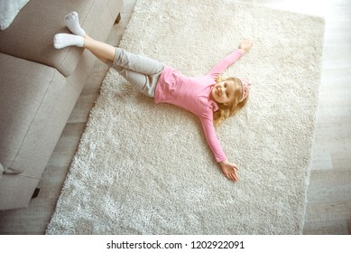 Top view of cute little princess relaxing on comfortable rug at home. She is putting feet of couch and stretching hands sideways. Child is laughing