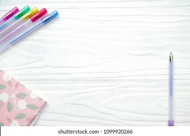 Top view of cute pink notebook and set color of pen on white wood background. Back to school. Mock up. Copy space.