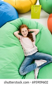 top view of cute redhead girl lying on bean bag chair and smiling at camera
