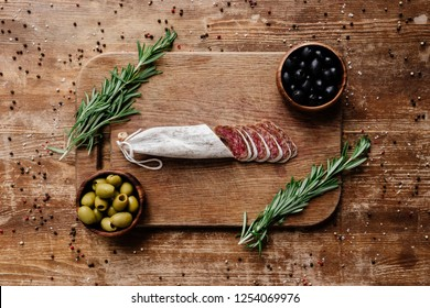 top view of cutting board with rosemary, black and green olives in two bowls and delicious sliced salami on wooden table with scattered spices