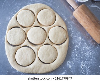 Top view of cutting dough into round pieces with rolling pin and flour on bakery working table