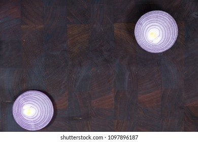 top view of dark brown butchers cutting board with chopped red onion in 