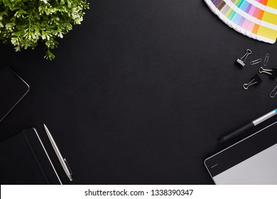 Top view of dark table graphic designer with color sampler, tablet and diary with copy space. Flat lay shot on black background