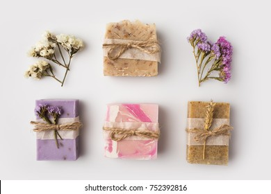 top view of decorated homemade soap with flowers on white surface