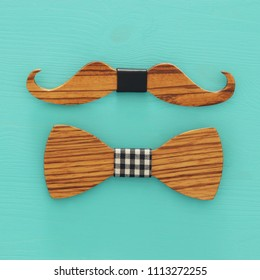 Top view of decorative wooden male bowtie and moustache over blue background