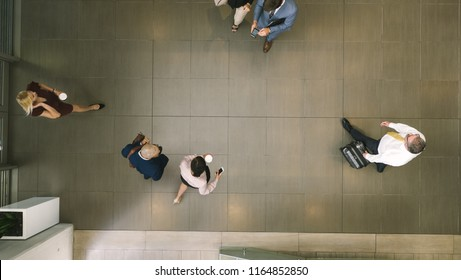 Top view of defocused business people in a lobby. Business people walking through a office hallway.