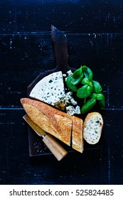 Top view of delicious blue cheese with fresh basil and bread slices on dark wooden chopping board over old grunge background, flat lay.