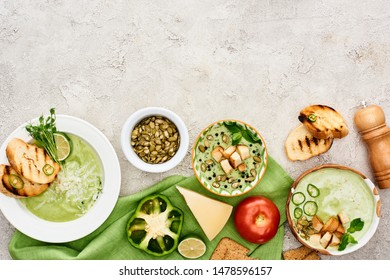top view of delicious creamy green soup served with vegetables and croutons on green napkin