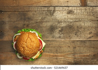 Top view delicious hamburger on wooden background. Fastfood meal. Vintage toned