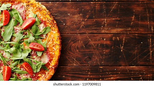 Top view of delicious italian pizza served on dark brown wooden table with copy space