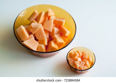 Top view delicious juicy fresh melon ready for eating. One big orange bowl with big cut pieces and a small cup with smaller bites.