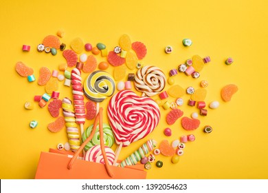top view of delicious multicolored candies scattered from paper bag on bright yellow background
