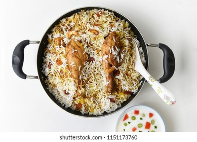 Top view of delicious North Indian food Hydrabadi chicken biryani, Dum Biriyani, Chicken pulao seasoned with mint leaves, basmati rice, herbs, raitha for Ramadan Kareem, Eid-Ul-Adha