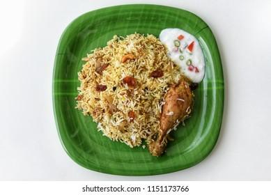 Top view of delicious North Indian food Hydrabadi chicken biryani, Dum Biriyani, Chicken pulao seasoned with mint leaves, basmati rice, herbs, raitha for Ramadan Kareem, Eid-Ul-Adha