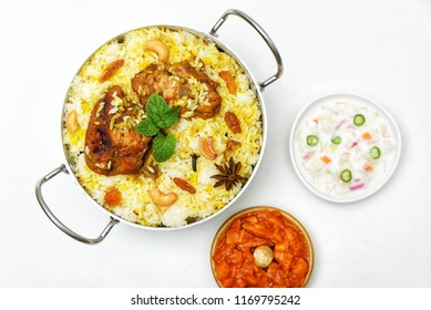 Top view of delicious North Indian food Hydrabadi chicken biryani, Dum Biriyani, Chicken pulao seasoned with mint leaves, basmati rice, herbs, raitha for Ramadan Kareem, Eid-Ul-Adha feast Iftar party