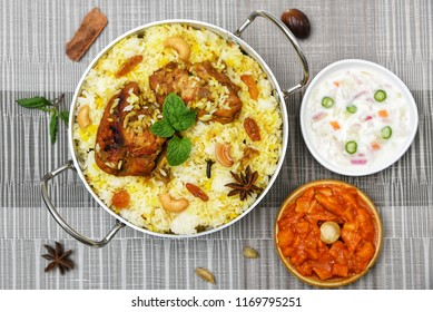 Top view of delicious North Indian food Hydrabadi chicken biryani, Dum Biriyani, Chicken pulao seasoned with mint leaves, basmati rice, herbs, raitha for Ramadan Kareem, Eid-Ul-Adha feast Iftar party