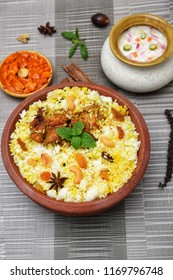 Top view of delicious North Indian food Hydrabadi chicken Dum biryani in clay pot. Chicken pulao seasoned with mint leaves, basmati rice, herbs, raitha for Ramadan Kareem, Eid-Ul-Adha Iftar party